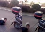 شاهد.. امرأة تعاقب ابنها بِجرِّه خلف دراجة نارية!